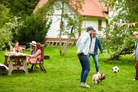 leisure, holidays, people and pets concept - happy friends playing football with dog at summer garden party Stock Photo