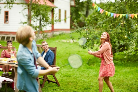 holiday house: leisure, holidays, people and sport concept - happy friends playing badminton or shuttlecock at summer garden party