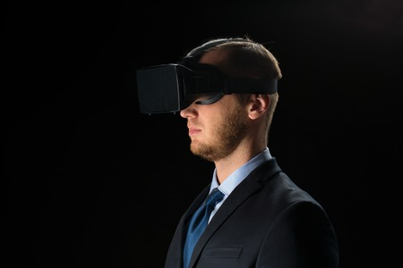 mediated: 3d technology, virtual reality, cyberspace and augmented reality concept - young businessman with virtual reality headset or 3d glasses over black background