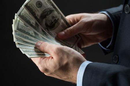 사람, 비즈니스, 재정 및 돈 개념 - 검정 배경 위에 달러 현금을 들고 사업가 손을 가까이