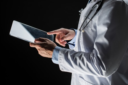 futuristic: healthcare, people, technology and medicine concept - close up of male doctor in white coat with stethoscope and tablet pc computer over black background Stock Photo
