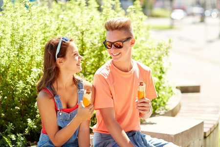couple outdoor: fast food, summer and people concept - happy teenage couple eating hot dogs sitting on city street bench Stock Photo