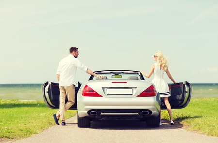 transport, travel, road trip and people concept - happy man and woman near cabriolet car at sea side Stock Photo