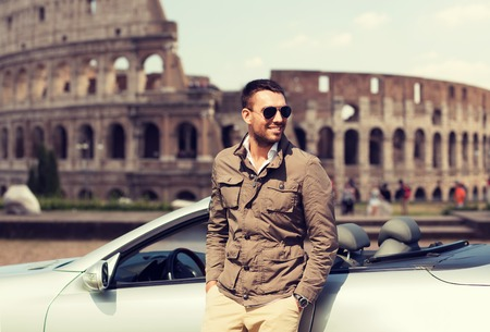 trip over: travel, tourism, road trip, transport and people concept - happy man near cabriolet car over coliseum in rome background Stock Photo