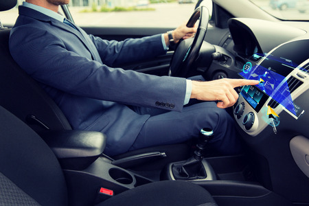 electronic: transport, business trip, navigation, technology and people concept - close up of young man in suit driving car and using gps navigator system on board computer screen Stock Photo