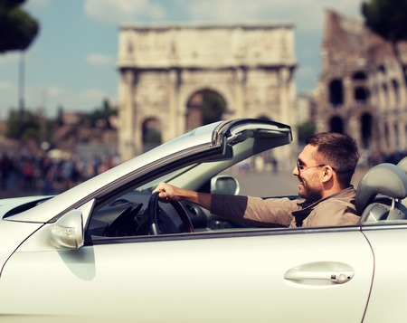 trip over: travel, tourism, road trip, transport and people concept - happy man driving cabriolet car over triumphal arch in city of rome background Stock Photo
