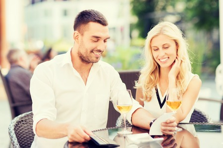 date, people, payment, holidays and relations concept - happy couple with wallet and wine glasses looking at bill at restaurant terrace Stock Photo