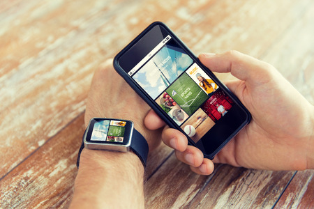 business, technology, media and people concept - close up of male hand holding smart phone and wearing watch with news application