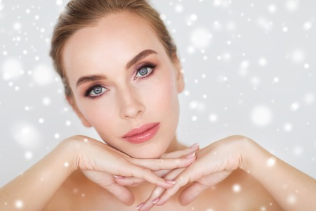 beauty, people, winter and bodycare concept - close up of beautiful young woman face and hands over gray background and snow