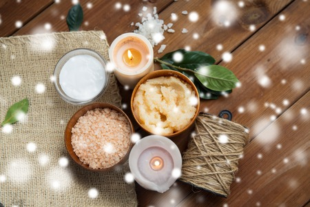 natural therapy: beauty, spa, therapy, natural cosmetics and wellness concept - body scrub with himalayan pink salt and candles on wood over snow