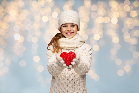 people, christmas, holidays, charity and love concept - smiling teenage girl in winter clothes with small red heart over lights background