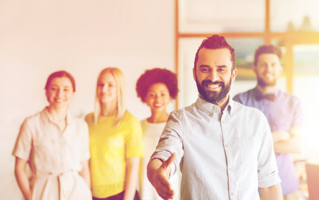 personas saludandose: negocio, puesta en marcha, la gente, el gesto y el concepto de trabajo en equipo - hombre joven y feliz con el saludo de la barba por apretón de manos sobre el equipo creativo en la oficina Foto de archivo
