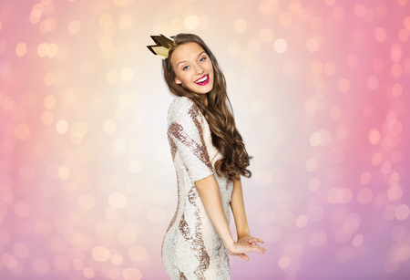majesty: people, holidays and celebration concept - happy young woman or teen girl in party dress and golden princess crown over rose quartz and serenity lights background