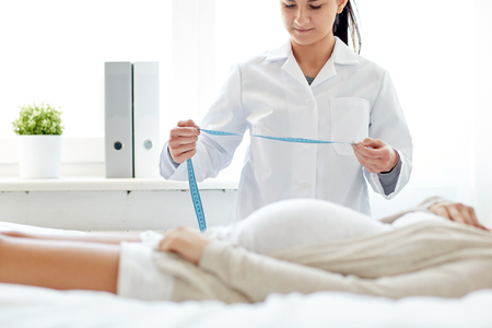 obstetrician: pregnancy, medicine, health care and people concept - close up of obstetrician doctor with centimeter tape measuring pregnant woman tummy at hospital