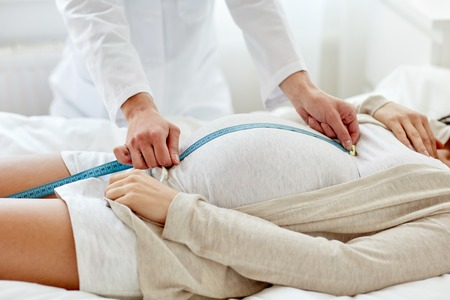 pregnancy, medicine, health care and people concept - close up of obstetrician doctor with centimeter tape measuring pregnant woman tummy at hospital