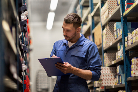 warehouses: car service, repair, maintenance and people concept - auto mechanic man or smith writing to clipboard at workshop or warehouse