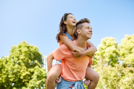 holidays, vacation, love and people concept - happy smiling teenage couple having fun at summer park