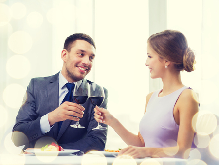 main course: restaurant, couple and holiday concept - smiling couple with main course and red wine at restaurant