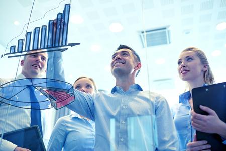 empleado de oficina: negocios, personas, trabajo en equipo y la planificación concepto - sonriendo equipo de negocios de dibujo gráfico en el tablón de anuncios de la oficina Foto de archivo