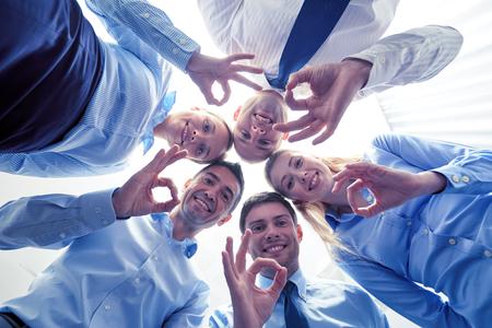 circulo de personas: negocio, la gente y el trabajo en equipo concepto - sonriente grupo de empresarios de pie en círculo Foto de archivo