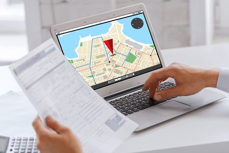 gprs: business, navigation, technology and people concept - businessman with gps navigator map on laptop computer screen working at office