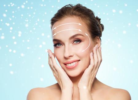 schoonheid, plastische chirurgie, facelift, mensen en verjonging concept - mooie jonge vrouw raakt haar gezicht met het heffen van pijlen over blauwe achtergrond en sneeuw Stockfoto