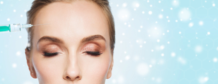 anti season: people, cosmetology, plastic surgery, anti-aging and beauty concept - beautiful young woman face and syringe making lifting injection to forehead over blue background and snow Stock Photo