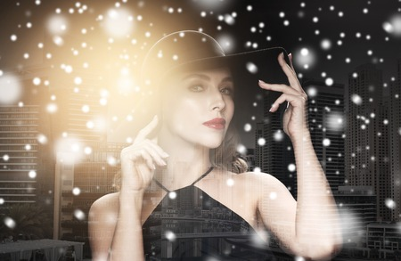 femme fatale: people, luxury and christmas concept - beautiful woman in black hat over dark over dubai city background double exposure with highlight and snow