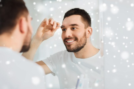 tweezing: beauty and people concept - smiling young man with tweezers tweezing eyebrow and looking to mirror at home bathroom over snow Stock Photo
