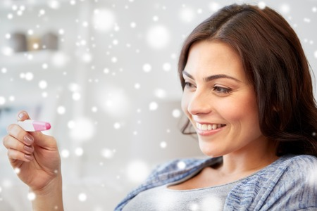 fertility, winter, maternity and people concept - happy smiling woman looking at pregnancy test at home over snow Stock Photo