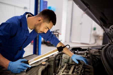 service de voiture, la réparation, l'entretien et les gens concept - auto mécanicien homme avec lampe de travail à l'atelier Banque d'images