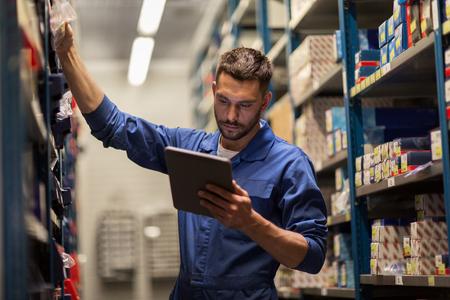 servizio di auto, riparazione, manutenzione e persone Concetto - meccanico uomo o fabbro con il computer tablet pc alla ricerca di pezzi di ricambio in laboratorio o magazzino