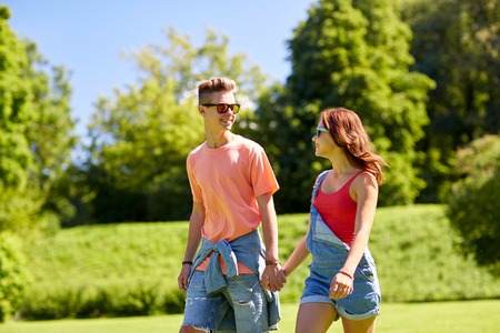 holidays, vacation, love and people concept - happy smiling teenage couple walking and looking at each other in summer park Stock Photo