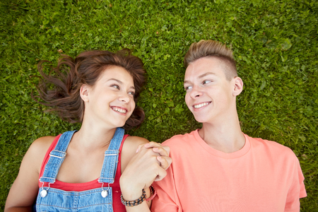 love and people concept - happy teenage couple lying on grass at summer Stock Photo
