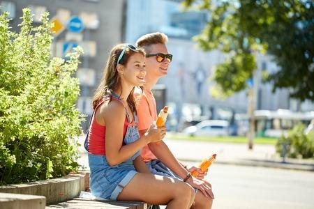 pareja de adolescentes: comida rápida, el verano y el concepto de la gente - pareja feliz de comer perros calientes adolescentes que se sientan en banco de la calle de la ciudad Foto de archivo