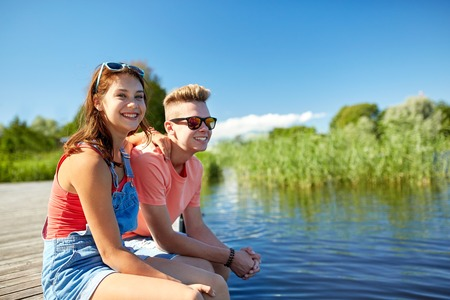 teenage couple: holidays, vacation, love and people concept - happy teenage couple sitting on river berth at summer