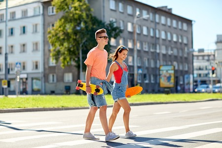 popular: summer holidays, extreme sport and people concept - happy teenage couple with short modern cruiser skateboards crossing city crosswalk