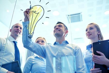 inspiracion: negocios, personas, trabajo en equipo y la planificación concepto - sonriendo equipo de negocios con el marcador y la bombilla del doodle de trabajo en la oficina