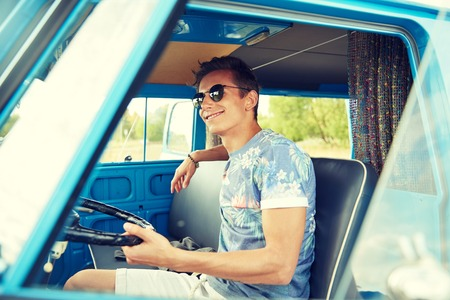 minivan: summer holidays, road trip, vacation, travel and people concept - smiling young hippie man driving in minivan car