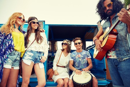 trip over: summer holidays, road trip, vacation, travel and people concept - happy young hippie friends having fun and playing music over minivan car Stock Photo