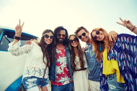 summer sign: summer holidays, road trip, vacation, travel and people concept - smiling young hippie friends over minivan car showing peace hand sign Stock Photo