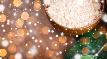 christmas light: beauty, spa, bodycare, bath and natural cosmetics concept - close up of himalayan pink salt in wooden bowl with leaves over lights and snow