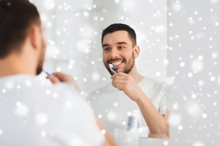 health care, dental hygiene, people and beauty concept - smiling young man with toothbrush cleaning teeth and looking to mirror at home bathroom over snow