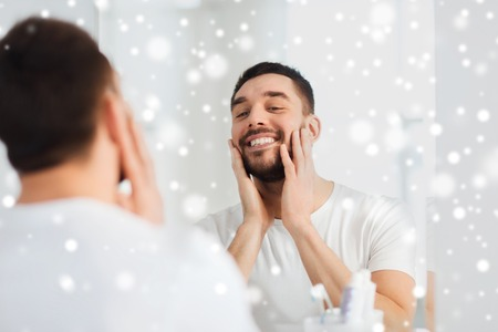 metrosexual: beauty, hygiene, shaving and people concept - smiling young man looking to mirror at home bathroom over snow