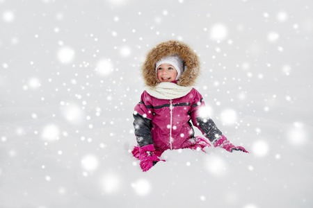 clothes winter: childhood, fashion, season and people concept - face of happy little kid or girl in winter clothes on snow Foto de archivo