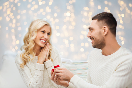 happy christmas: love, couple, relationship, proposal and holidays concept - happy man giving engagement ring in little red gift box to woman over christmas tree and lights background