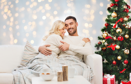 lovely couple: family, holidays, love and people concept - happy couple covered with plaid hugging on sofa over christmas tree and lights background Stock Photo