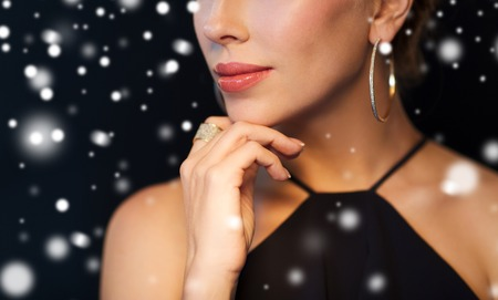 celebrities: people, luxury, christmas, holidays and jewelry concept - close up of beautiful woman wearing diamond earring and ring over black background and snow Stock Photo
