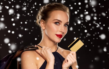 people, luxury, christmas, holidays and sale concept - beautiful woman with credit card and shopping bags over black background and snow Stock Photo
