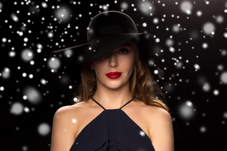 femme fatale: people, christmas, holidays, luxury and fashion concept - beautiful woman in hat over black background and snow